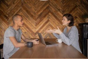 Two people talk and exchange ideas during a meeting.