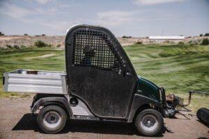 A man driving a golf cart on a course
