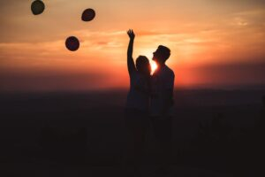 a couple with balloons at sunset