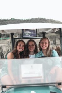 A group of teenage girls in a golf cart