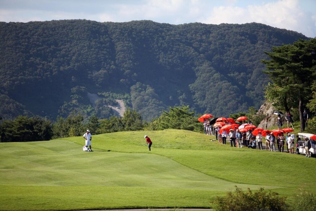 A golf tournament being watched by an audience near the course