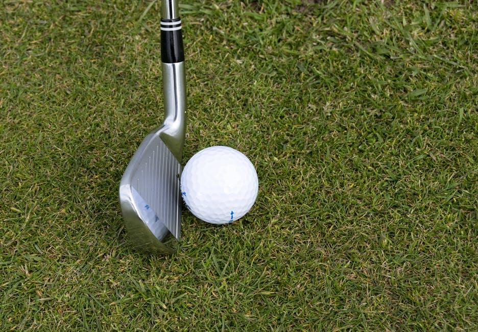 A close-up of a golf club and golf ball on a golf course.