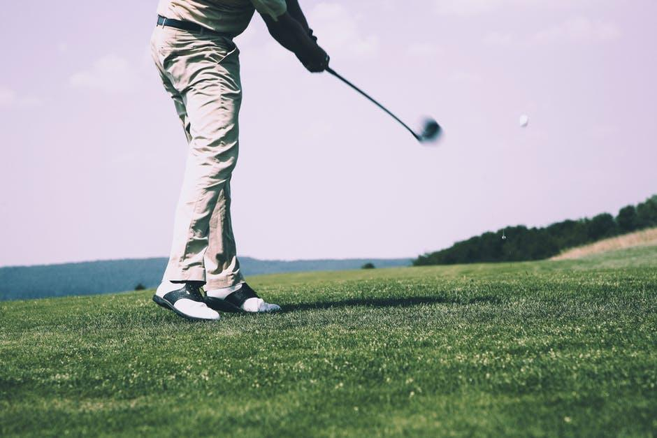 A man plays golf with no people in his vicinity.