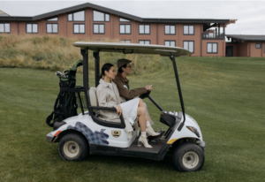 A couple is cruising through a green area in a residential neighborhood in their golf cart