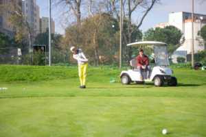 A woman just hit a golf ball towards a hole, and a man is waiting for his turn in a golf cart while watching her play.