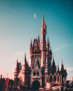 The classic Disney Castle under a crescent moon.