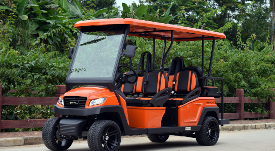Orange Bintelli Beyond 6PR Street Ready Golf Cart parked in front of the fenced leafy area.