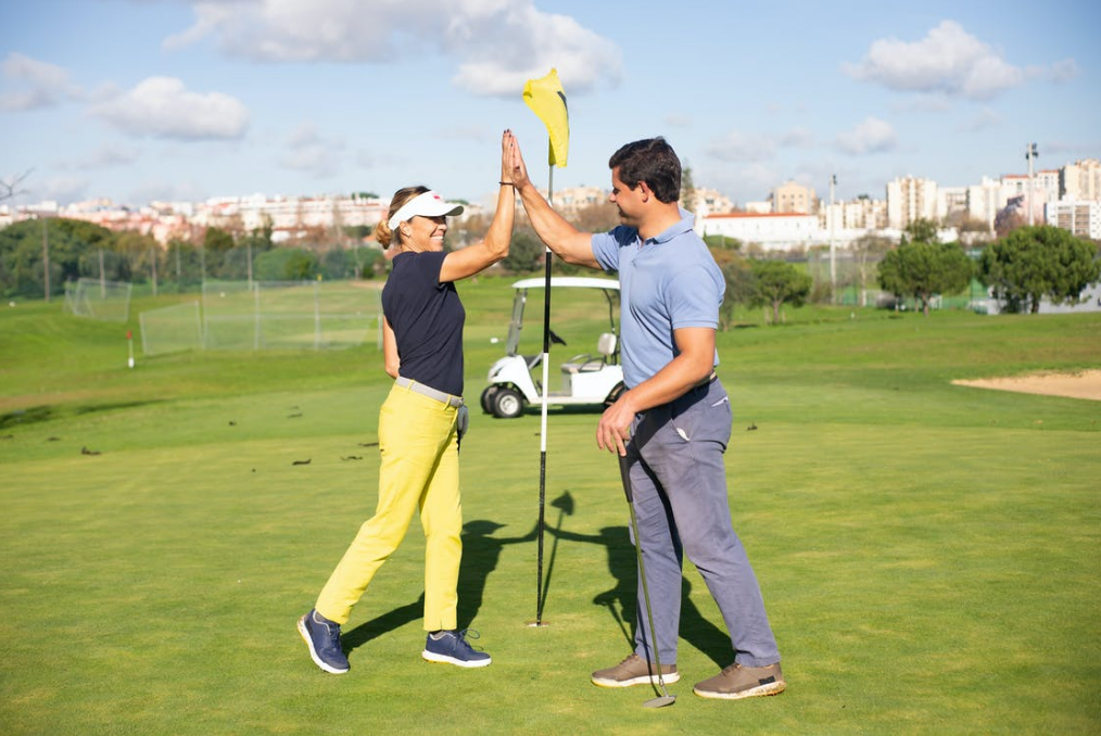 A man and a woman are high-fiving at a golf hole cheerfully in front of their golf cart.