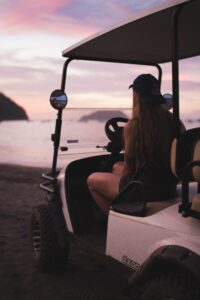 girl riding a golf cart at the beach