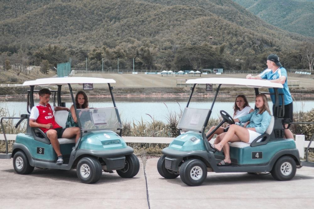 Young people enjoying golf carts off the golf course.